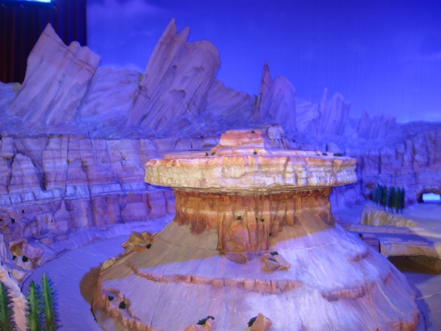 A much larger 1:8 model of Radiator Springs model is behind the smaller Carsland model.